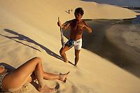 Fisherman sells a fish to a female tourist taking sun at Jericoacoara beach dunes, Ceara coastline, northeastern Brazil.