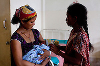 Amrita Rokya (left), 18, cradles her 2-day-old baby in the Bardia District Hospital, one hour's walk from her village in Bardia, Western Nepal, on 29th June 2012. In Bardia, StC works with the district health office to build the capacity of female community health workers who are on the frontline of health service provision like ante-natal and post-natal care, and working together against child marriage and teenage pregnancy especially in rural areas. Photo by Suzanne Lee for Save The Children UK