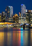 The lights of the Trade and Convention Center and other downtown buildings reflect on the water of Coal Harbour in Vancouver, British Columbia, Canada