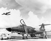 """On the flight line, United States Air Force technicians prepare a McDonald RF-101 Voodoo for a photo reconnaissance mission.  Overhead, a Fairchild C-123 Provider takes off on another assault airlift sortie, providing an air bridge to an outpost in South Vietnam.  High above, a Cessna O-1E """"Bird Dog"""" returns after pointing out Viet Cong targets to pilots of strike aircraft on January 6, 1967..Credit: U.S. Air Force via CNP"""