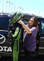 Jun 18, 2016; Bristol, TN, USA; NHRA funny car driver Alexis DeJoria (left) is helped with safety gear by daughter Isabella DeJoria during qualifying for the Thunder Valley Nationals at Bristol Dragway. Mandatory Credit: Mark J. Rebilas-USA TODAY Sports