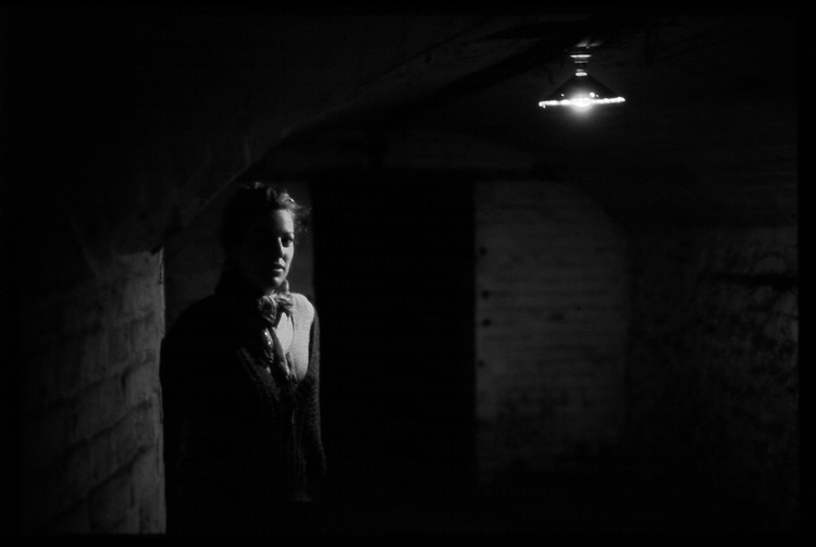 A young woman waiting alone in a dark room with a single light