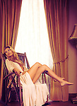 Romantic portrait of a beautiful sensual woman sitting in a rocking chair by the window