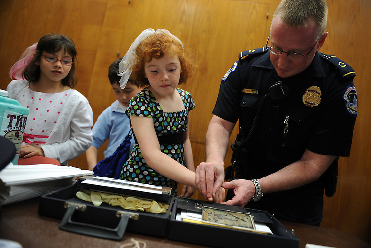 "Sophia Ayoud, 8, gets fingerprinted by Capitol Police Officer Howard Liebengood as brother Gabriel, 8, and Amina, 8, wait their turns during ""Kid Safety Day,"" held in Dirksen, April 24, 2008.  The triplets are children of Laura Ayoud of the Senate Legislative Counsel."