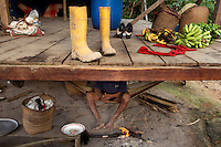 A Waorani (Huaroni) man sits by a fire beneath a house in Gabaro.