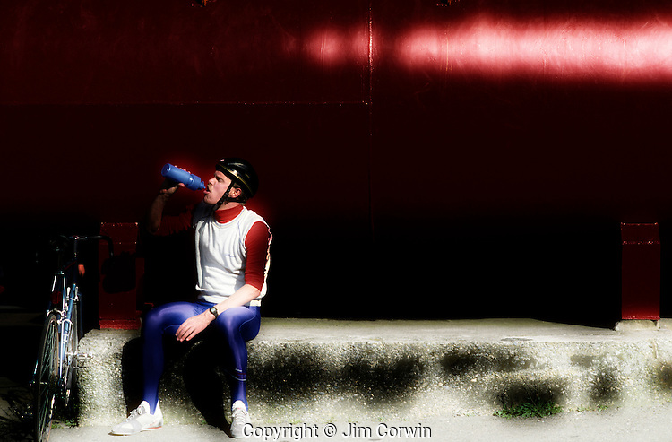 Bicyclist taking a drink of water after a hard ride sitting in front of red metal container in th 80's retro gear