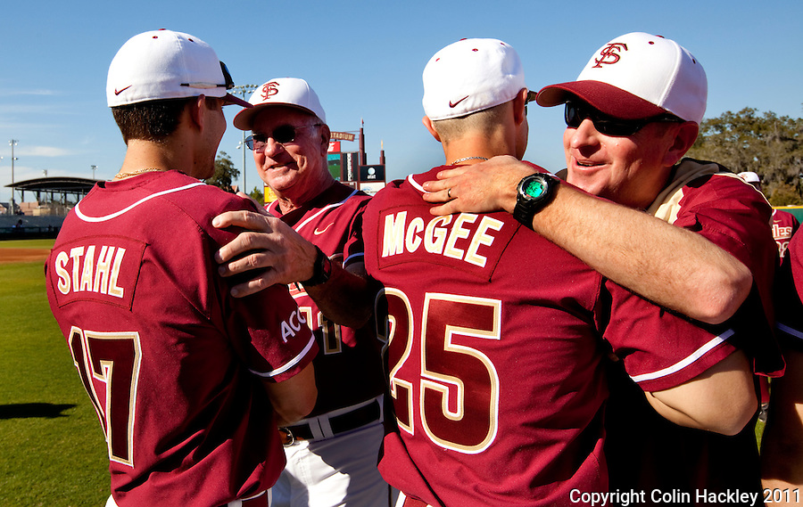 TALLAHASSEE, FL 2/18/11-FSU-VMI BASE11 CH-Florida State Head Coach Mike Martin, second from left, and his son Assistant Coach Mike Martin, Jr, right, spoke to each of their players prior to the Virginia Military Institute game Friday at Dick Howser Stadium in Tallahassee. The Seminoles beat the Keydets 12-0 in the season opener for both teams..COLIN HACKLEY PHOTO