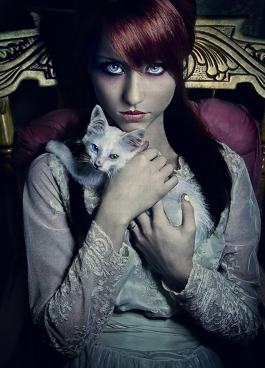 Female youth with long red hair holding a small white cat