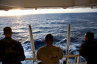 Sailors look out at the ocean during a break on board the USNS Comfort, a naval hospital ship, before its mission to help survivors of the earthquake in Haiti on Monday, January 18, 2010 in the Atlantic Ocean off the coast of the United States.