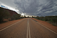 A storm passes overhead at Uluru/Ayers Rock, seen from the perimeter road in the late afternoon