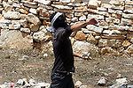 A Palestinian protester throws stones towards Israeli soldiers during clashes following a protest against the expropriation of Palestinian land by Israel on March 31, 2013 in the village of Kfar Qaddum, near the occupied West Bank city of Nablus. Photo by Issam Rimawi