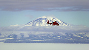 A United States Coast Guard helicopter is seen against the backdrop of Mt. Discovery, across McMurdo Sound from McMurdo Station on Friday, Jan. 12, 2001. Helicopters are a lifeline to the outlying camps in areas near McMurdo station, but bad weather can ground them for days at a time.  Goes with weather notes, to be filed saturday. Ernie Mastroianni photo.