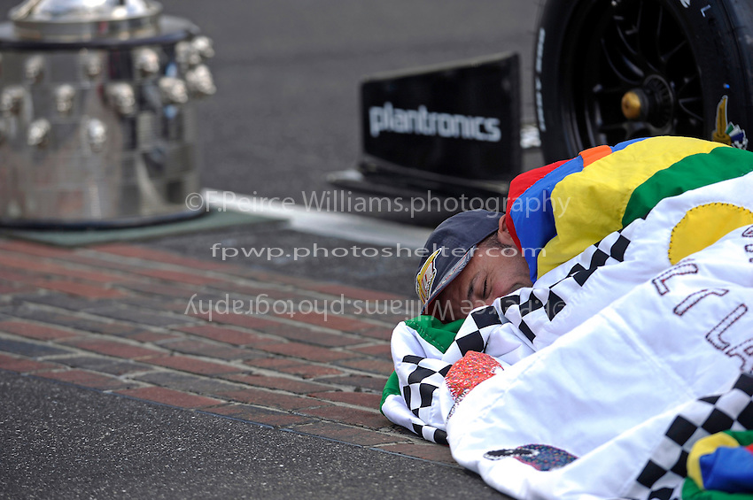 "Race winner Tony Kanaan (#11) feigns sleeping under the race quilt on the ""Yard of Bricks""."