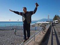 Italy. Liguria Region. Bordighera. An elderly bald bearded man walks in balance on a stainless steel rail. A child is on the beach near the Mediterranean Sea. 27.12.16 © 2016 Didier Ruef