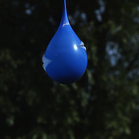 Series of an exploding blue balloon with water inside.