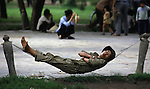 A soldier on home leave rests in a jungle hammick strung between two chain posts in Lenin Park in Hanoi, North Vietnam. (Jim Bryant Photo).....