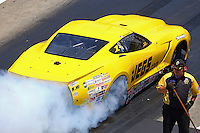 Jun 18, 2016; Bristol, TN, USA; NHRA pro mod driver Troy Coughlin does a burnout past an NHRA safety safari crew member during qualifying for the Thunder Valley Nationals at Bristol Dragway. Mandatory Credit: Mark J. Rebilas-USA TODAY Sports