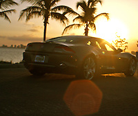 Fisker stunning electric car on the waterfront in miami heading into a bright setting sun