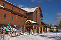 Old Faithful Snow Lodge in winter, with snow coach and skis at entrance; Yellowstone National Park, Wyoming. .#D0401530