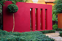 The contemporary rendered vermillion wall planted with clipped box hedging makes a bold statement in the garden