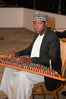 Zanzibar, Tanzania.  Taarab Musicians.  Culture Musical Club. Qanun Player, wearing a traditional Zanzibari hat, a kofia.