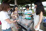Volunteers and dive staff participating in  the Team Tyura Sango coral reef restoration project enjoy a barbeque on the municipal beach at Onna Village, Okinawa Prefecture, Japan, on Saturday, June 23, 2012. Photographer: Robert Gilhooly