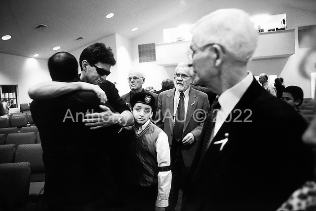 Conyers, Georgia.USA.April 2, 2003..The father, Jorge Rincon, of Diego Fernando Rincon who was one of four soldiers killed in Iraq by a suicide car-bomber, attends a memorial service for his son at Conyers Adventist Church. He was accompanied by his two surviving sons, George (10 - in red sweater) and Fabian (20), The father asked the community to help him and his family to contend with the unbearable pain. Many came out to do just that.
