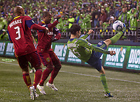 Seattle Sounders FC midfielder Alvaro Fernandez kicks the ball over Real Salt Lake defender Robbie Russell and midfielder Andy Williams during play in a Major League Soccer Wester Conference Semifinal match at CenturyLink Field in Seattle Wednesday November 2, 2011. The Sounders won the match 2-0, but lost the series.