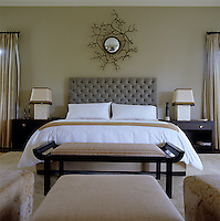 The master bedroom is decorated in tranquil neutral colours and has a mirror by Herve van der Straten
