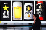 A woman walks past a poster advertising Sapporo Breweries Ltd.'s beer