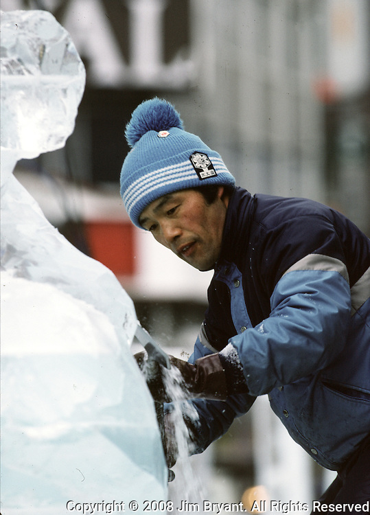 An ice carver uses a chisel to chip and smooth a sculpture. These are not traditional Frosty the Snowmen, but huge carved and chiseled Samurai Warriors, Buddhists gods, historical heroes of fairy tales and Walt Disney characters. Some stand as big as buildings. Chiseled out of tons of packed snow, the sculptures are the pride and job of the residents of Sapporo, Japan, who hosts the world famous Ice and Snow Sculpture Festival for five days in early February.Themes of the sculptures are picked from Kabuki stages, historical characters or fairy tales. (Jim Bryant Photo).....