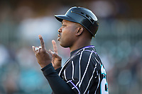 Charlotte Knights coach Garey Ingram (25) lets the runner know there are two out during the game against the Norfolk Tides at BB&T BallPark on May 2, 2017 in Charlotte, North Carolina.  The Knights defeated the Tides 8-3.  (Brian Westerholt/Four Seam Images)