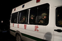 Riot police ride in an armored bus on the streets of Urumqi, Xinjiang, China.