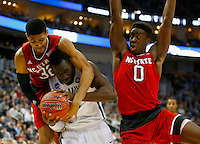PITTSBURGH, PA - MARCH 21:  Daniel Ochefu #23 of the Villanova Wildcats is pressured by Kyle Washington #32 and Abdul-Malik Abu #0 of the North Carolina State Wolfpack in the first half during the third round of the 2015 NCAA Men's Basketball Tournament at Consol Energy Center on March 21, 2015 in Pittsburgh, Pennsylvania.  (Photo by Jared Wickerham/Getty Images)