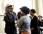Waterbury, CT- 21 April 2017-042117CM06-  Captain Lawrence Hunter has his badge pinned on by his daughter Lauren, as his wife Tanesha looks on during a promotion ceremony at the City Hall on Friday.  Joining the police department in June of 1995, Captain Hunter spent most of career in the patrol division. He rose through the ranks while working in dispatch and being a Field Training Officer to new police recruits.  The lifelong resident of Waterbury earned a bachelors degree in Psychology and a Master Degree in Forensic Psychology.  Captain Hunter has also donated his time and energy by mentoring youth, officiating and coaching numerous youth teams.  Also included in the ceremony were: Assistant Deputy Chief Edward Apicella, Captains Robert Maxwell and Michael Ponzillo;  Lieutenants Jeremy Desena and Gary Angon; Sergeants Ryan Bessette, Nadine Amatruda, Michael Sobol, Tierone Touponse, Marc Fortini, Paul Calo, Jason Prescott and Frank Laone Jr.   Christopher Massa Republican-American
