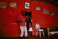Amador Ballumbrosio, 65, is known for his Afro-Peruvian music learning to play from his grandfather when he was four years old.  and today teaches children.  The music he first learned was like the blues, but he says the dance of the community is now more upbeat. His grand daughter watches as he plays in the living room of his home. The community of El Carmen is made up of slave descendants from Africa.  They are known for their Afro-Peruvian music and dance.