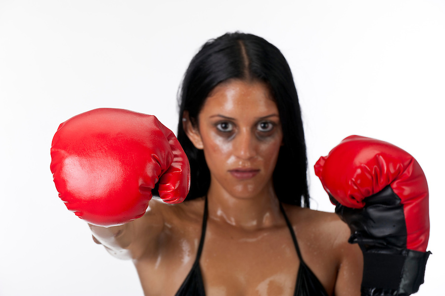 Hispanic woman boxing with gloves. Use of selective focus, focus on the glove.