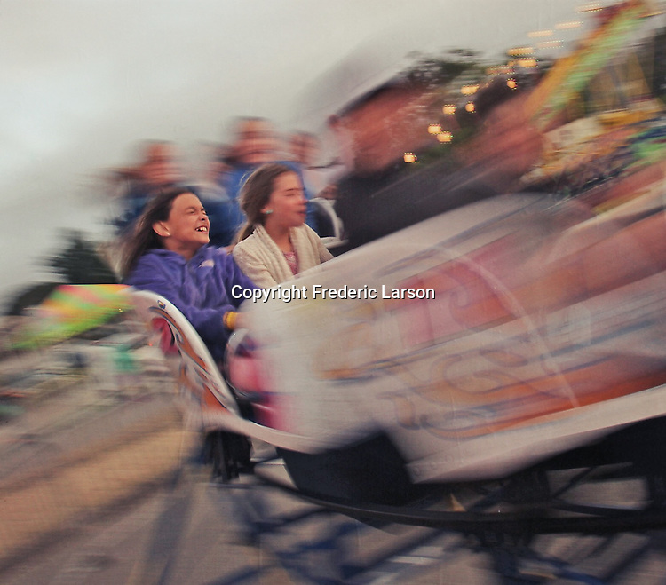 Two girls enjoy a roller coaster ride at the Mill Valley carnival during Memorial Day Weekend.