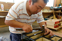 An artisan applying metalwork fittings to a chest of drawers, Iwayado Tansu Seisakujo, Oshu City, Iwate Prefecture, Japan, July 18, 2013. Iwayado Tansu chests of drawers have been made in the city of Oshu since the 1780s. They are noted for their fine lacquer finish and finely-wrought metalwork fittings.