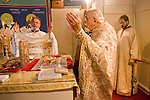 Liturgy service at St. Sava Orthodox Church, Jackson, Calif...Father Stephen Tumbas, Very Reverend Stavrofor Miladin Garich, at the altar with arms raised during the preparation of the sacrament as Dan Stojanovich watches from behind.