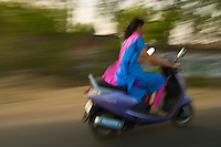 On the road from Mandava to Delhi, India, IndianWomen with sari on a scooter