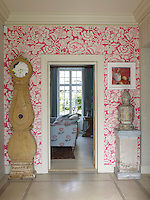 The entrance hall is decorated in a hot pink floral wall paper and a Swedish Mora clock
