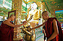 Two young monks touch a holy golden rabbit. After at least a year and not before the age of 20, a samanera will be considered for the higher Bhikkhu ordination.