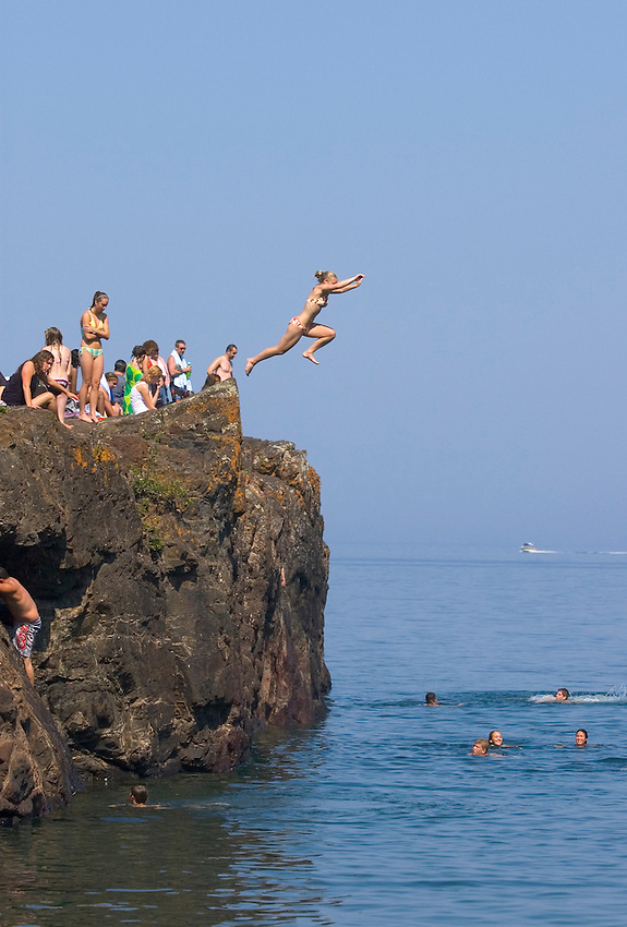 A girl jumps into Lake Superior at the Black Rocks area of Presque Isle Park in Marquette, Mich. on a hot summer day.