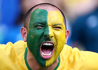 A Brazil fan cheers his side on before kick off