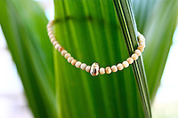 ivory and gold bracelet against a palm tree leaf