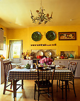 The table in the bright yellow kitchen has a blue and white checked tablecloth and is laid for breakfast