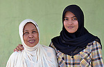 Nurul Aina (right) and her grandmother in Banda Aceh, Indonesia. Aina was just 8 years old in 2004 when a massive tsunami swept over the city, killing her parents and two siblings and leveling their home. Aina was fortunately visiting relatives in a neighborhood far from the seashore when the tsunami hit. With assistance from the Katahati Institute and Diakonie Katastrophenhilfe, a new house was built and titled in Aina's name, an accomplishment that required considerable legal advocacy by Katahati staff. As a result, rental income from the house has paid for Aina's schooling while she lives with her grandmother. Now 18, Aina is studying English at a local university, and plans to move into her house some day. The tsunami killed 221,000 people in Aceh province and left more than 500,000 displaced.