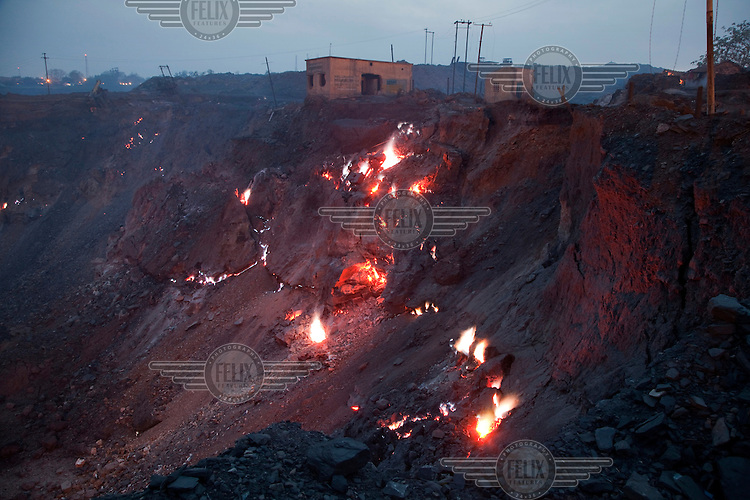 Buildings collapse into a fiery abyss. Due to the spread of open pit mining in areas where underground mines were previously operated, thousands of uncontrolled coal fires have broken out as oxygen has access to formerly covered seams of coal. The fires also ignite newly exhumed coal resulting in an estimated 30% loss before the coal can be transported away from the mines. Anti-mining activists claim that the coal companies are deliberately letting these fires spread in order to force people off the land and out of the areas where they want to excavate more open pit mines. The government has issued a moratorium on more open pit mines until existing fires can be brought under control, but in the race for quick profits, and with the cost and difficulty of putting out the fires, some of which have been burning for 100 years, most mining operations are ignoring this. ..