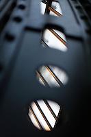 Plant History Glasshouse (formerly Australian Glasshouse), 1830s, Rohault de Fleury, Jardin des Plantes, Museum National d'Histoire Naturelle, Paris, France. Detail of the vaulted metal strut supporting the glass and metal roof. Through the gaps of the strut may be seen the glass and metal roof lit by the sunset.